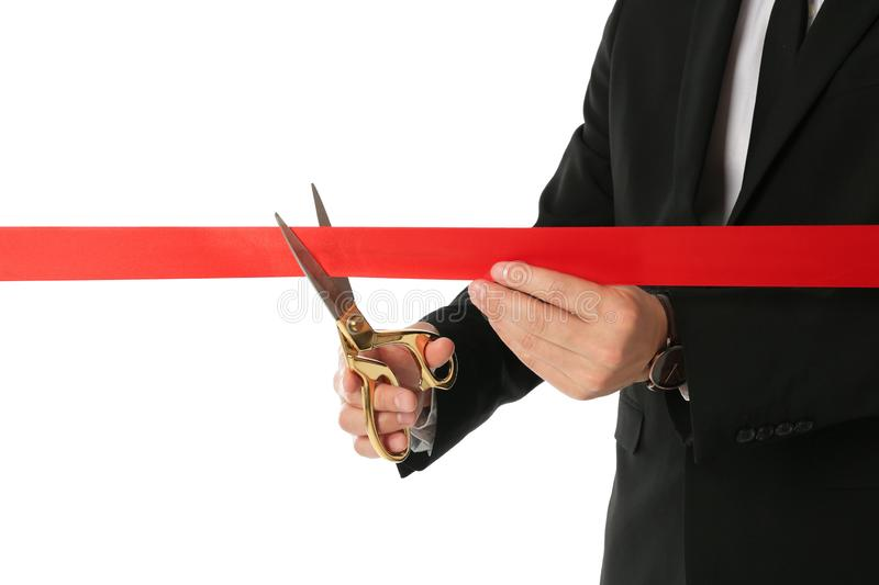 Man in office suit cutting red ribbon isolated on white. Closeup royalty free stock image