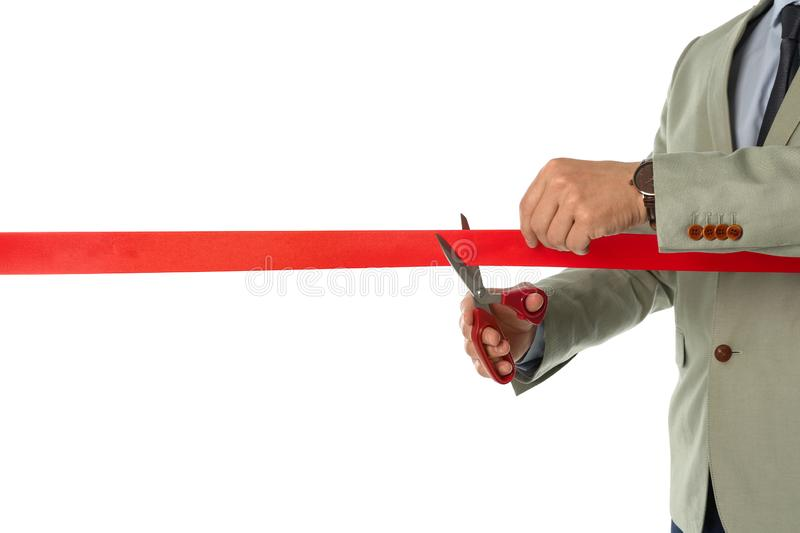 Man in office suit cutting red ribbon isolated on white. Closeup stock photos