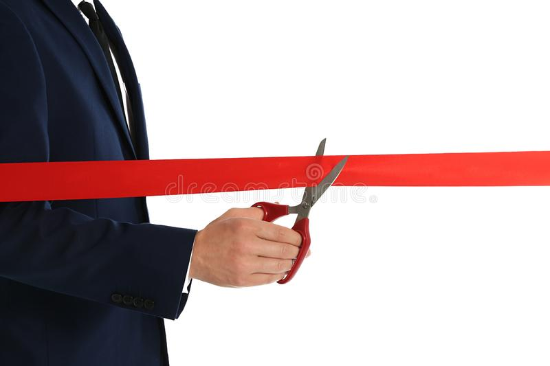 Man in office suit cutting red ribbon  on white. Closeup royalty free stock photos