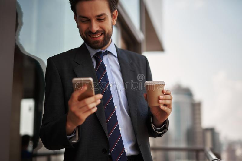Man in office suit reading massages on phone. Take a pause. Close up portrait of cheerful businessman reading massages on smartphone while standing on office royalty free stock images