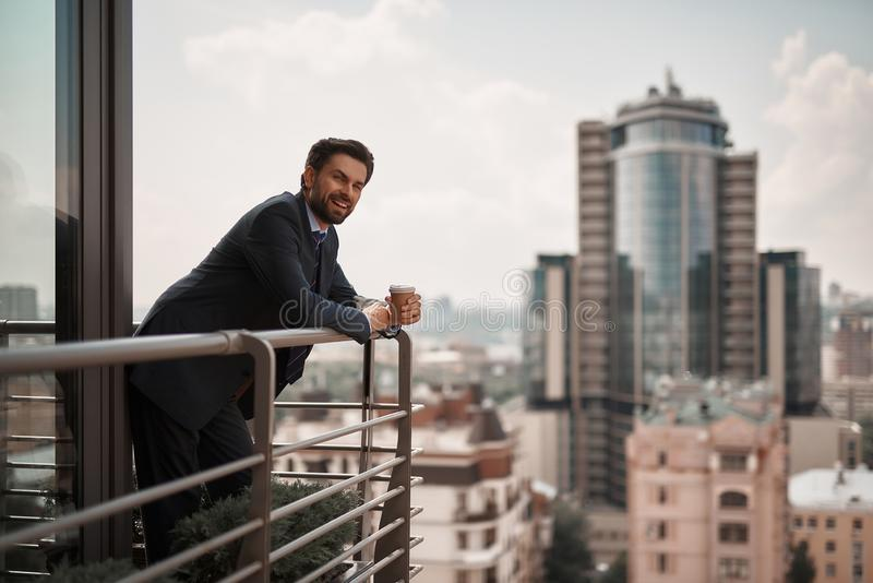 Man in office suit standing on balcony royalty free stock image