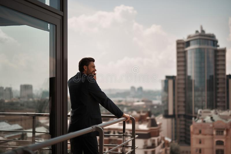 Man in office suit talking by phone on balcony. Take a pause. Back side portrait of businessman talking by phone while standing on office balcony. Copy space on royalty free stock images