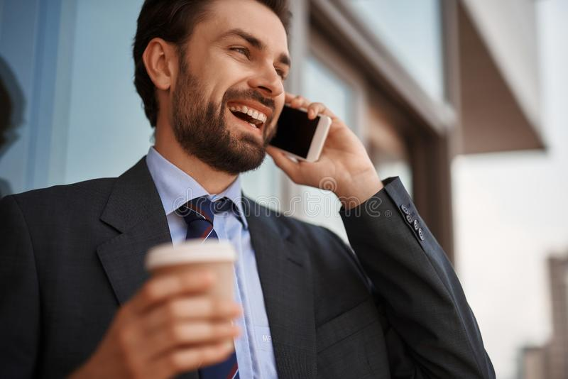 Man in office suit talking by phone on balcony. Take a pause. Close up low angle portrait of cheerful businessman talking by phone while standing on office royalty free stock image