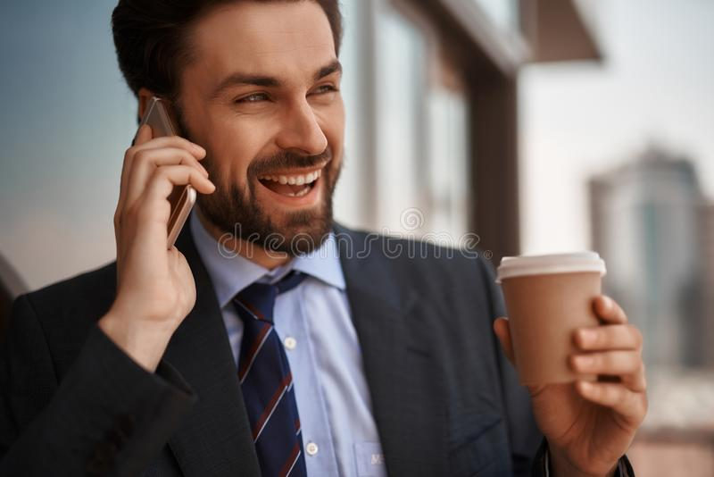 Man in office suit talking by phone on balcony. Take a pause. Close up portrait of cheerful businessman talking by phone while standing on office balcony with royalty free stock image