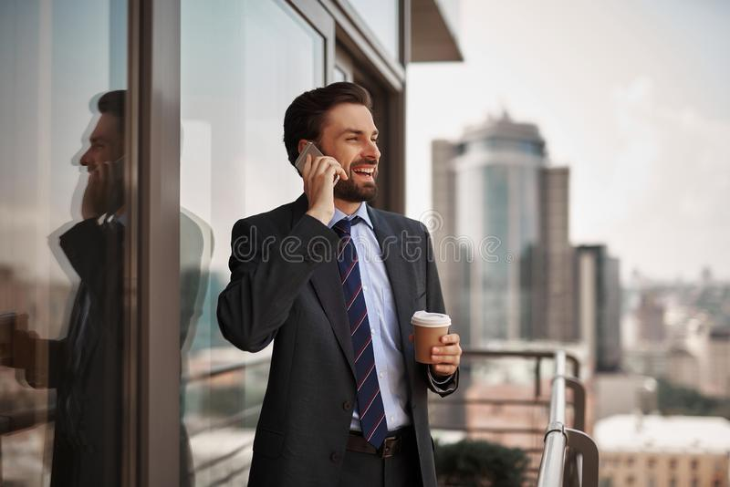 Man in office suit talking by phone on balcony royalty free stock image