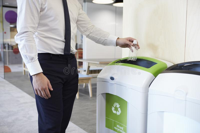 Man in an office throwing plastic bottle into recycling bin stock images
