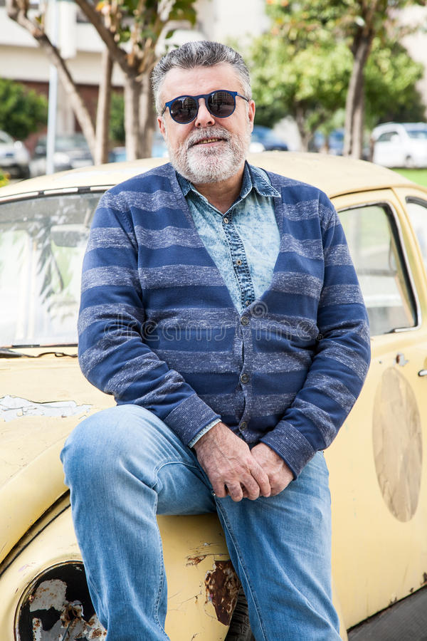 Man with an old classic yellow wolsvagen beetle. Man with an old classic yellow street wolsvagen beetle stock image
