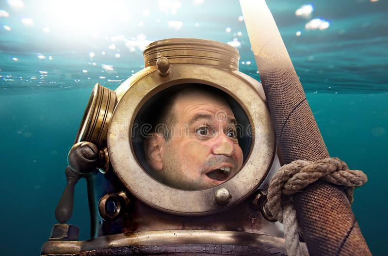 Man in old diving suit and helmet under water. stock photo