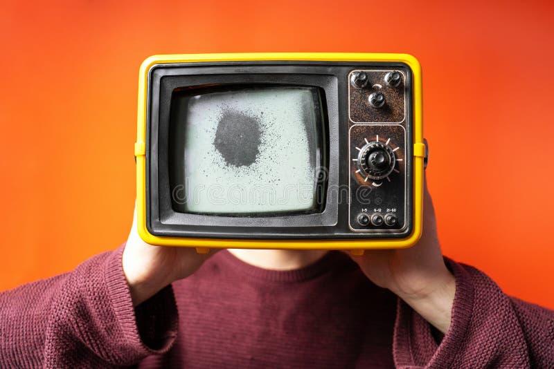 Man with old retro tv head with damaged screen on bright orange background, studio. Multimedia, brainwashing, social concept. stock photos
