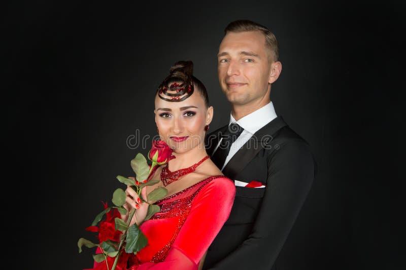 Man omhelzingsvrouw met rode roze bloem royalty-vrije stock afbeeldingen