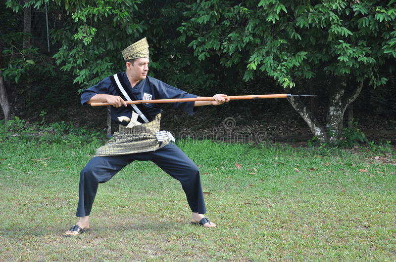 A man in a one of costume of Malaysia martial arts culture stock image
