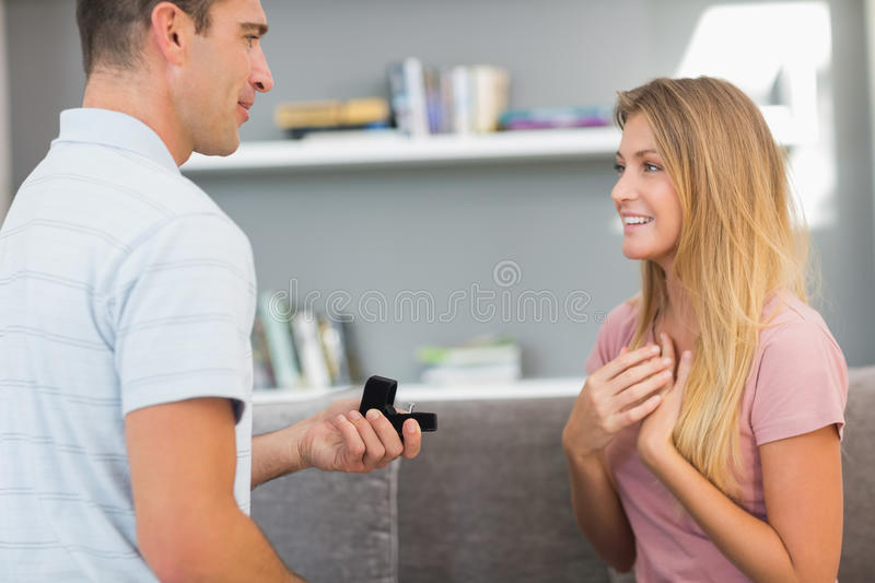 Man on one knee proposing to girlfriend. In sitting room at home royalty free stock photography