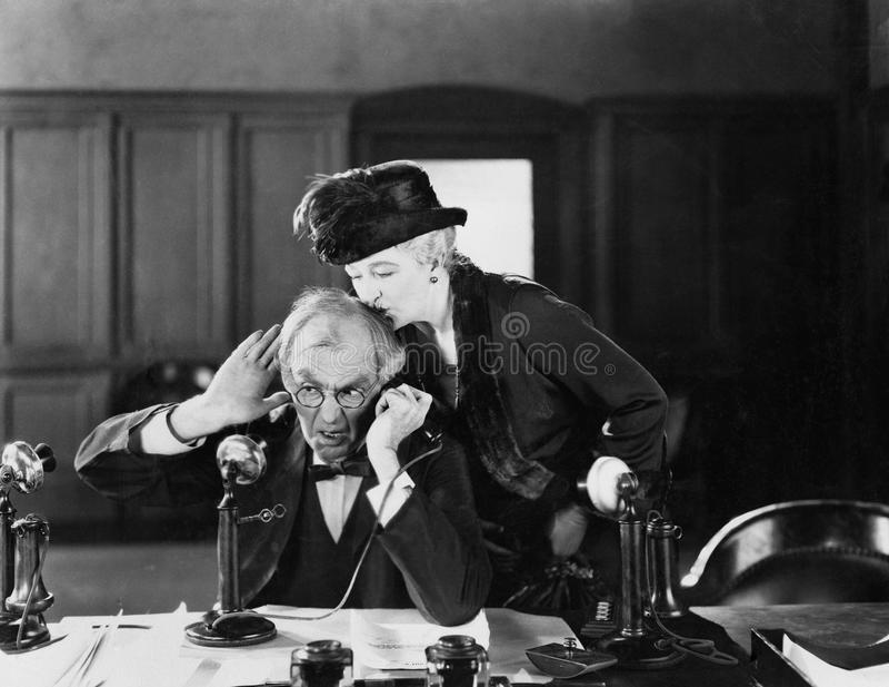 Man op een telefoon die door een vrouw op zijn hoofd worden gekust (Alle afgeschilderde personen leven niet langer en geen landgo stock foto's