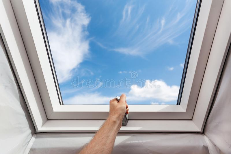 Man open new skylight mansard window in an attic room against blue sky. royalty free stock images