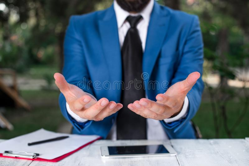 Man with opened hands in fron of the table. Mobile phone and notes on the table. Business concept with man in the suite. Man with opened hands in fron of the stock photo
