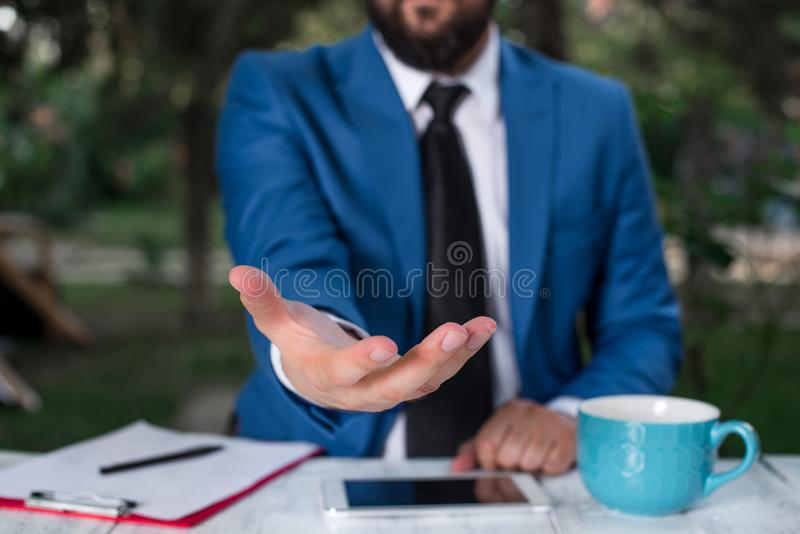 Man with opened hands in fron of the table. Mobile phone and notes on the table. Business concept with man in the suite. Man with opened hands in fron of the stock photography