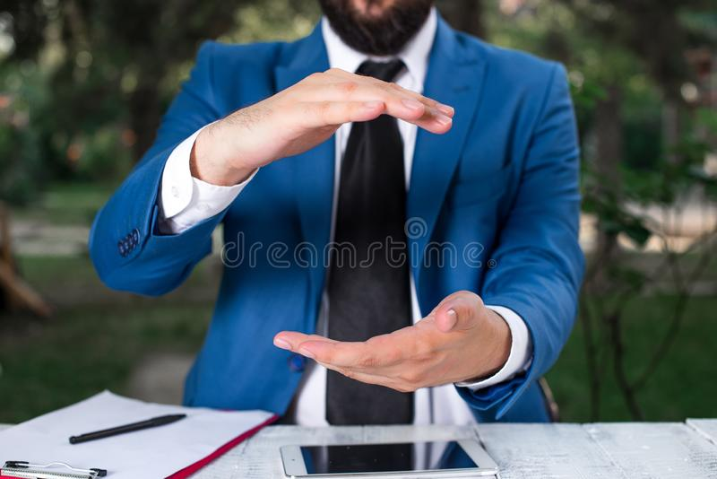 Man with opened hands in fron of the table. Mobile phone and notes on the table. Business concept with man in the suite. Man with opened hands in fron of the royalty free stock photo