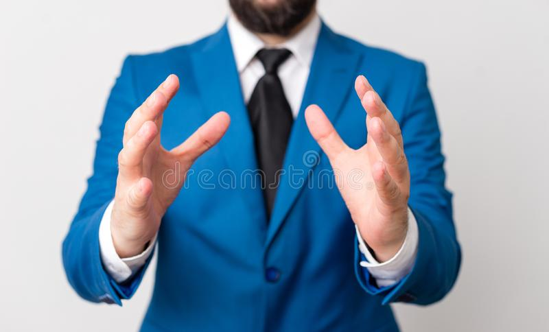 Man with opened hands in fron of the table. Mobile phone and notes on the table. Business concept with man in the suite. Man with opened hands in fron of the royalty free stock images