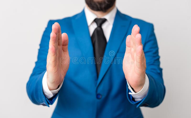 Man with opened hands in fron of the table. Mobile phone and notes on the table. Business concept with man in the suite. Man with opened hands in fron of the royalty free stock photography