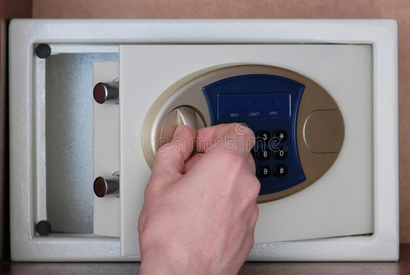 The man opened the safe hidden in the office in the closet to put the money. Close-up of the hand opening the door. Safety of. The man opened the safe hidden in royalty free stock image