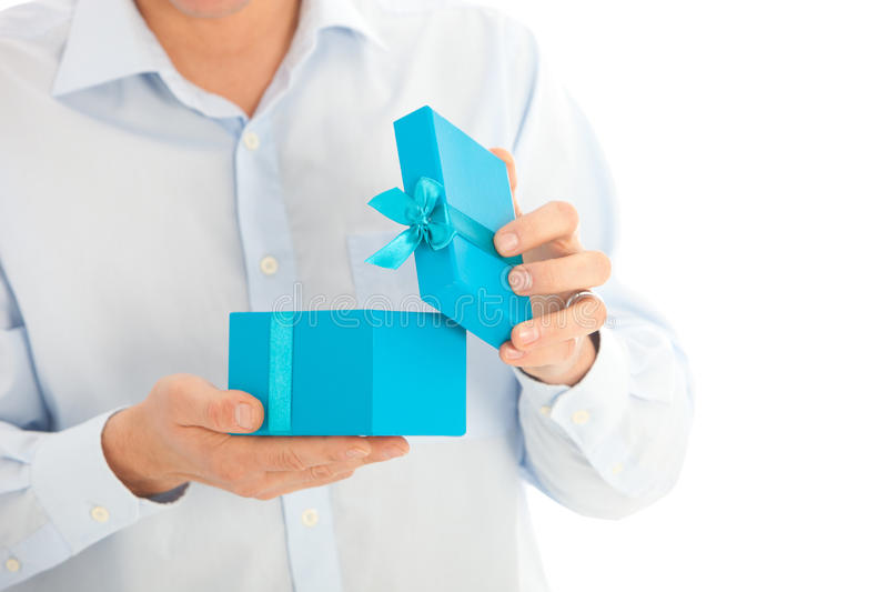 Man opening a birthday or Christmas gift. In a colourful turquoise blue box decorated with a ribbon and bow, close up torso view of his hands and the box royalty free stock photo