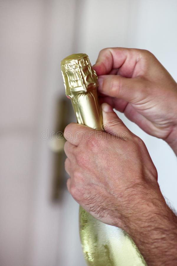 Man is opening a bottle of champagne. Waiter opens a bottle of wine. Man hands open bottle of champagne alcohol and wine drink. stock photos