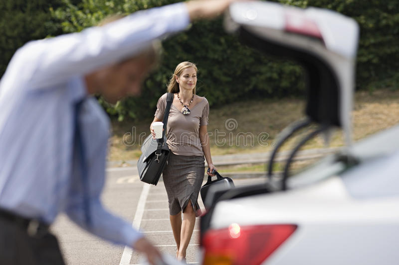Man opening car boot in car park, focus on businesswoman walking with luggage in background, smiling royalty free stock images