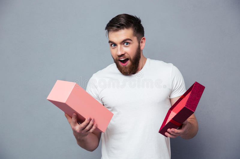 Man opening gift box. Portrait of a young man opening gift box over gray background royalty free stock photo