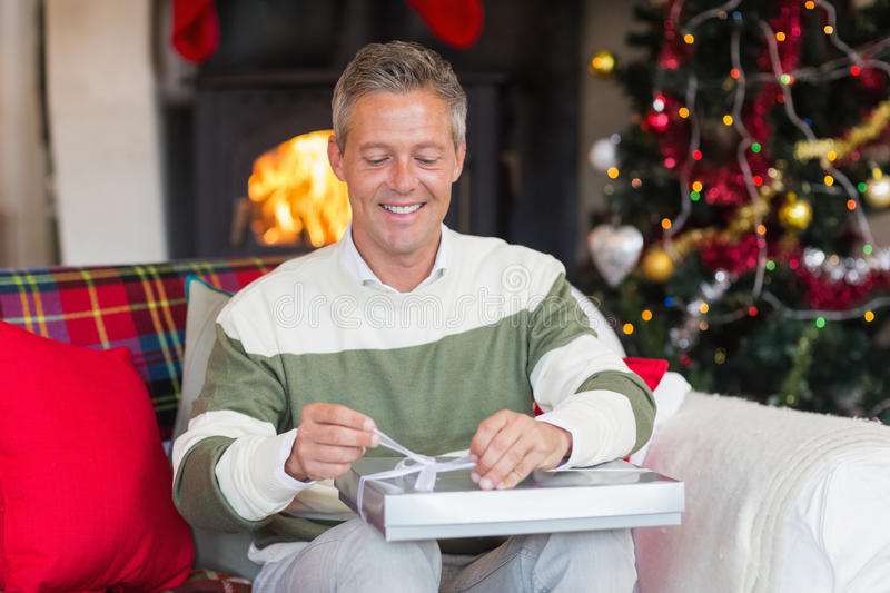 Man opening a gift on the couch at christmas. At home in the living room stock photography