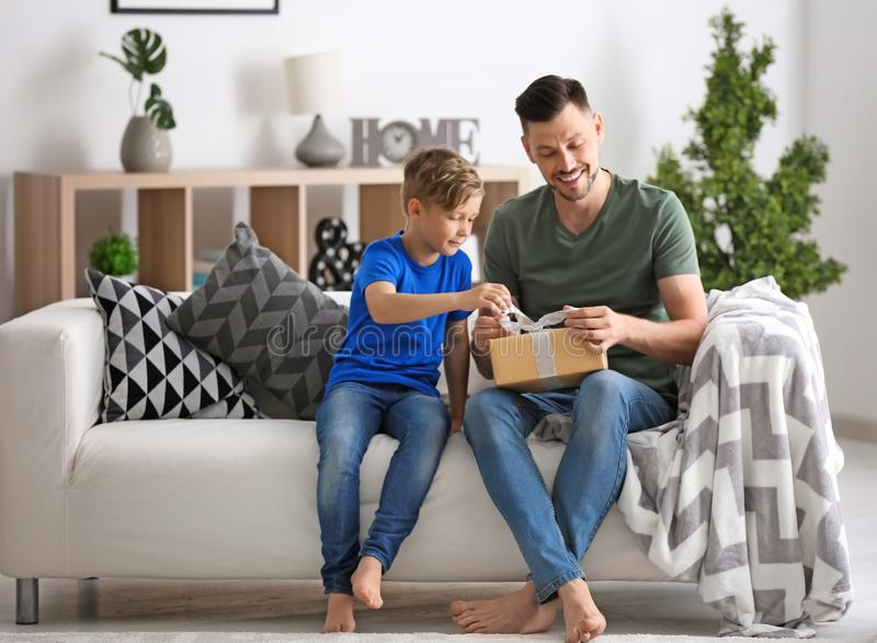 Man opening gift for Father's Day from his son at home royalty free stock images