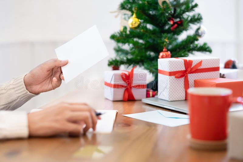 Man opening and sending christmas card. Christmas concept. Man wearing white sweater opening and sending christmas card royalty free stock images