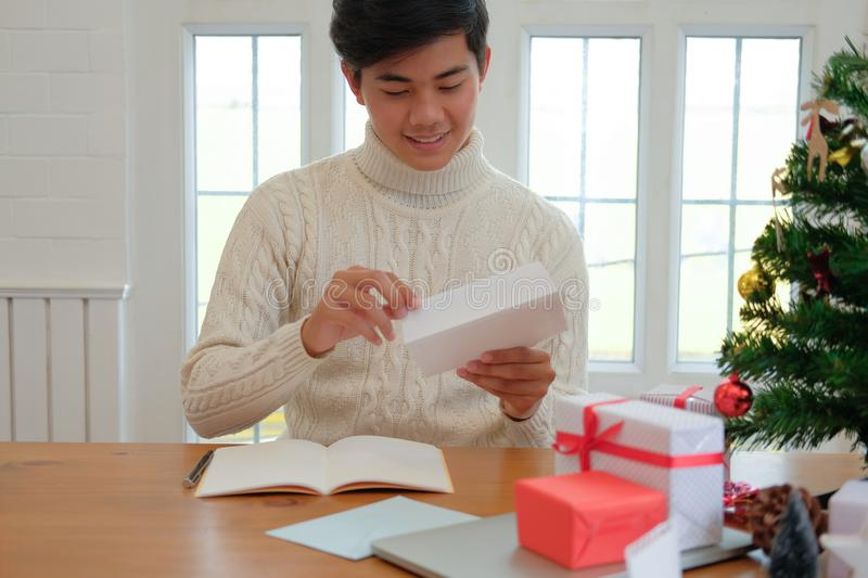 Man opening sending christmas letter greeting card holiday wishes with xmas decoration. Man wearing cream sweater opening sending christmas letter greeting card stock images