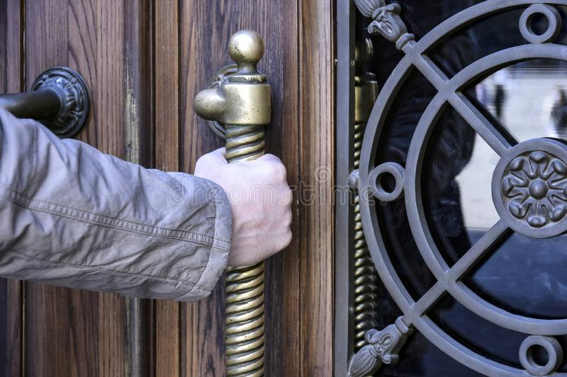 Man opens an ancient wooden door decorated with wrought iron elements and brass handle. Close-up. Selective focus royalty free stock photography