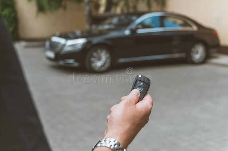 The man opens the car with a keychain, in the background is a black car. The man opens the car with a keychain, in the background is a black car royalty free stock image
