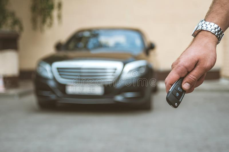 The man opens the car with a keychain, in the background is a black car and a yellow background. The man opens the car with a keychain, in the background is a royalty free stock images