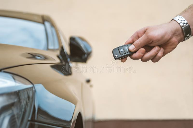 A man opens the car with a keychain, in the background is a yellow wall. A man opens the car with a keychain, in the background is a yellow wall royalty free stock images