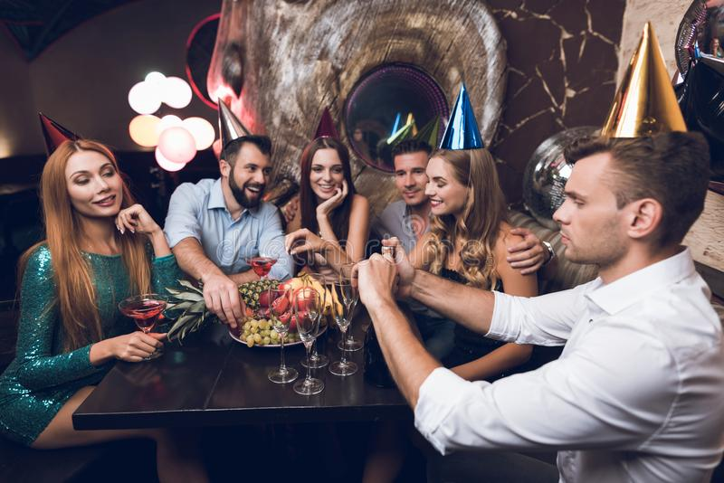The man opens champagne to drink with his friends. They sit in the club at the table and rest after the dance. The men opens champagne to drink with his friends stock photo