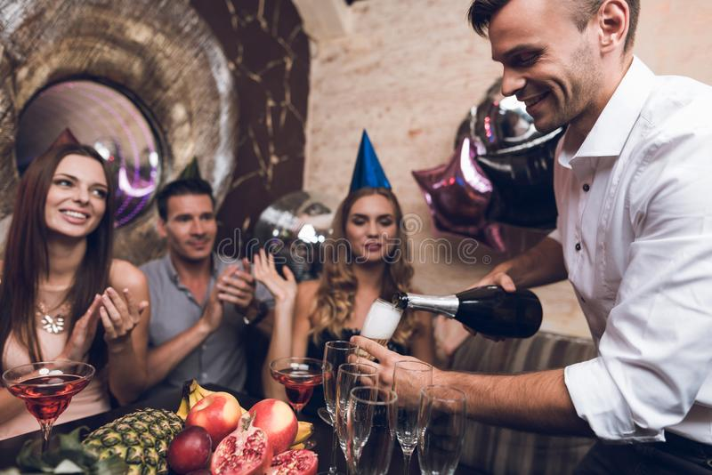 The man opens champagne to drink with his friends. They sit in the club at the table and rest after the dance. The men opens champagne to drink with his friends stock photography