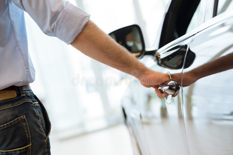 Man opens the door to a new car. Car inspection in the showroom royalty free stock images