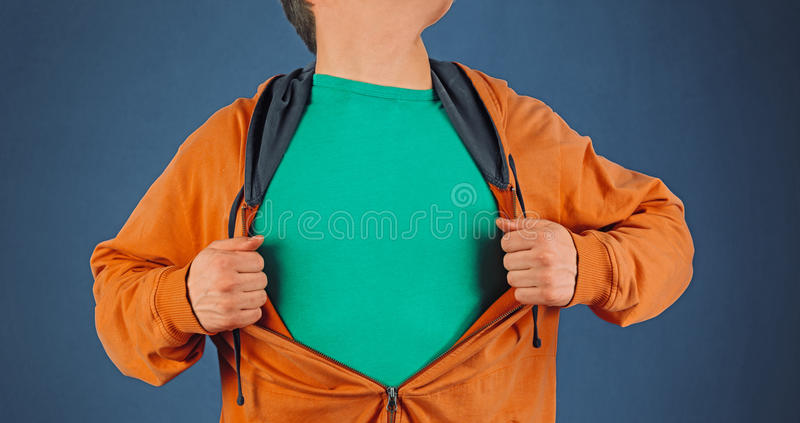 Man opens orange shirt, copyspace. Man opens shirt showing green t-shirt, space for text royalty free stock photography