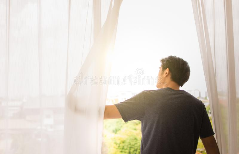 A man opens the window to see outside royalty free stock photo