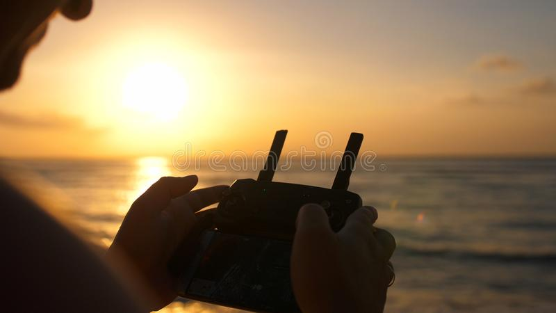 Close up of male hands operating a drone with remote control. Quadro copter drone flying over sunset ocean royalty free stock photography