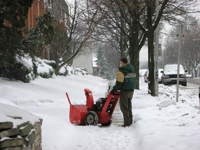 Man operating snow blower to clear driveway