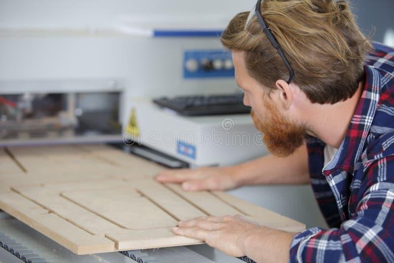 Man operating wood machine stock image