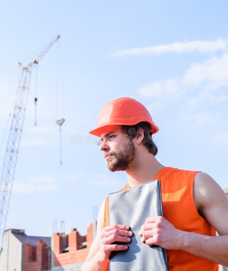 Man orange väst- och hjälmarbeten på konstruktionsplatsen Leverantörkontroll enligt plan Grabb i skyddande hjälm royaltyfria bilder