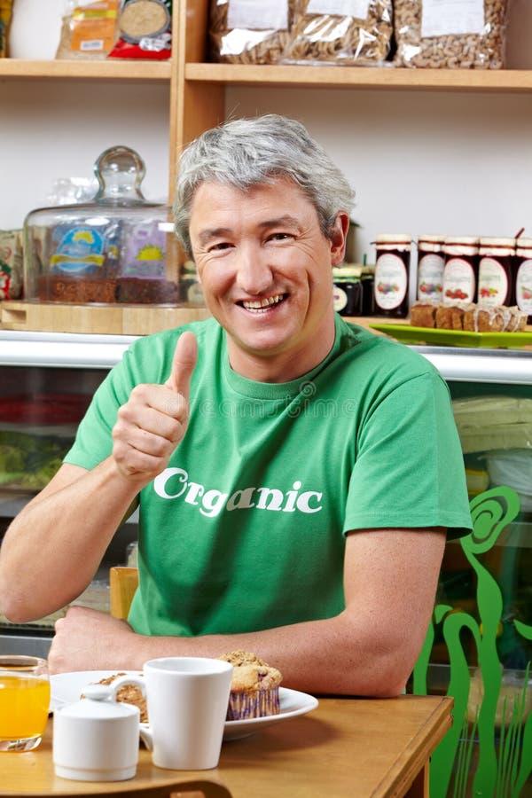 Man in organic café holding thumbs stock photos
