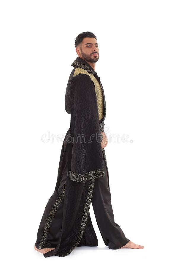 Man in oriental costume. Handsome strong courageous man in oriental costume stands on a white background stock photos