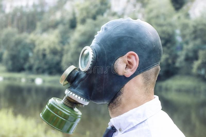 A man on outdoor in a gas mask. Bad ecology Air pollution, toxic emissions. royalty free stock photos