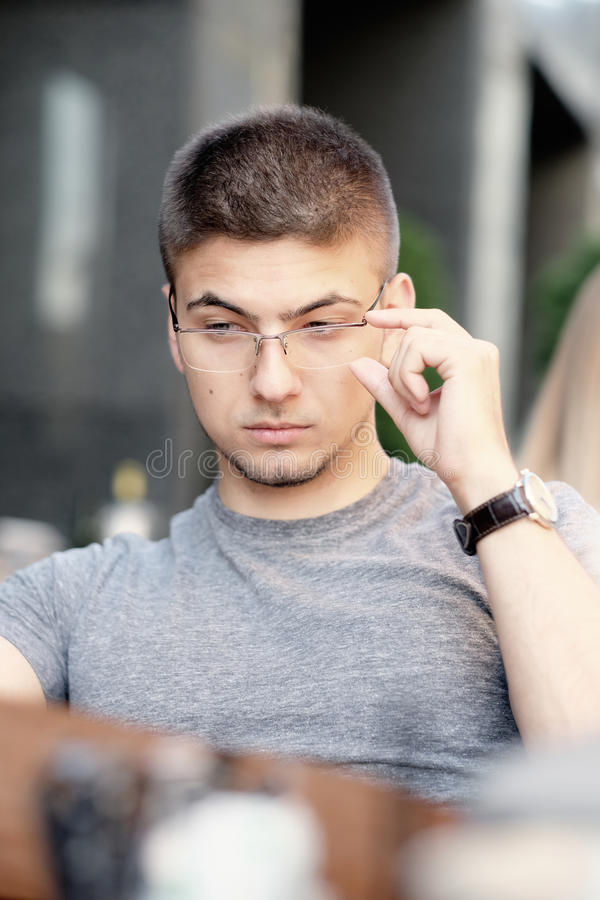 Man in outdoor restaurant looking at the menu. Young man in outdoor restaurant looking at the menu stock image