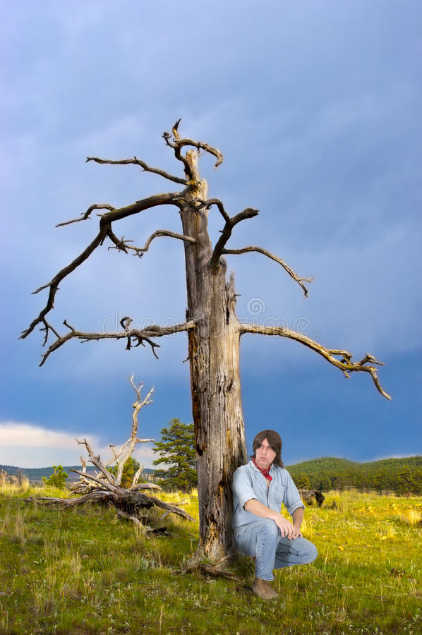 Man Outdoors in Wild Sit in Nature Mountain Meadow. An outdoors enthusiast sits outside and looks into the distance as he enjoys the quiet and peace of a royalty free stock photos